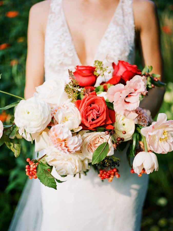 Genna with her red, pink and white wedding bouquet made by Lilia Flower Boutique, photographed with a Pentax 645m with Portra 400 film, developed and scanned by The Find Lab, wedding at Bar Lurcat, Minneapolis | ONONA Minneapolis film wedding photographer